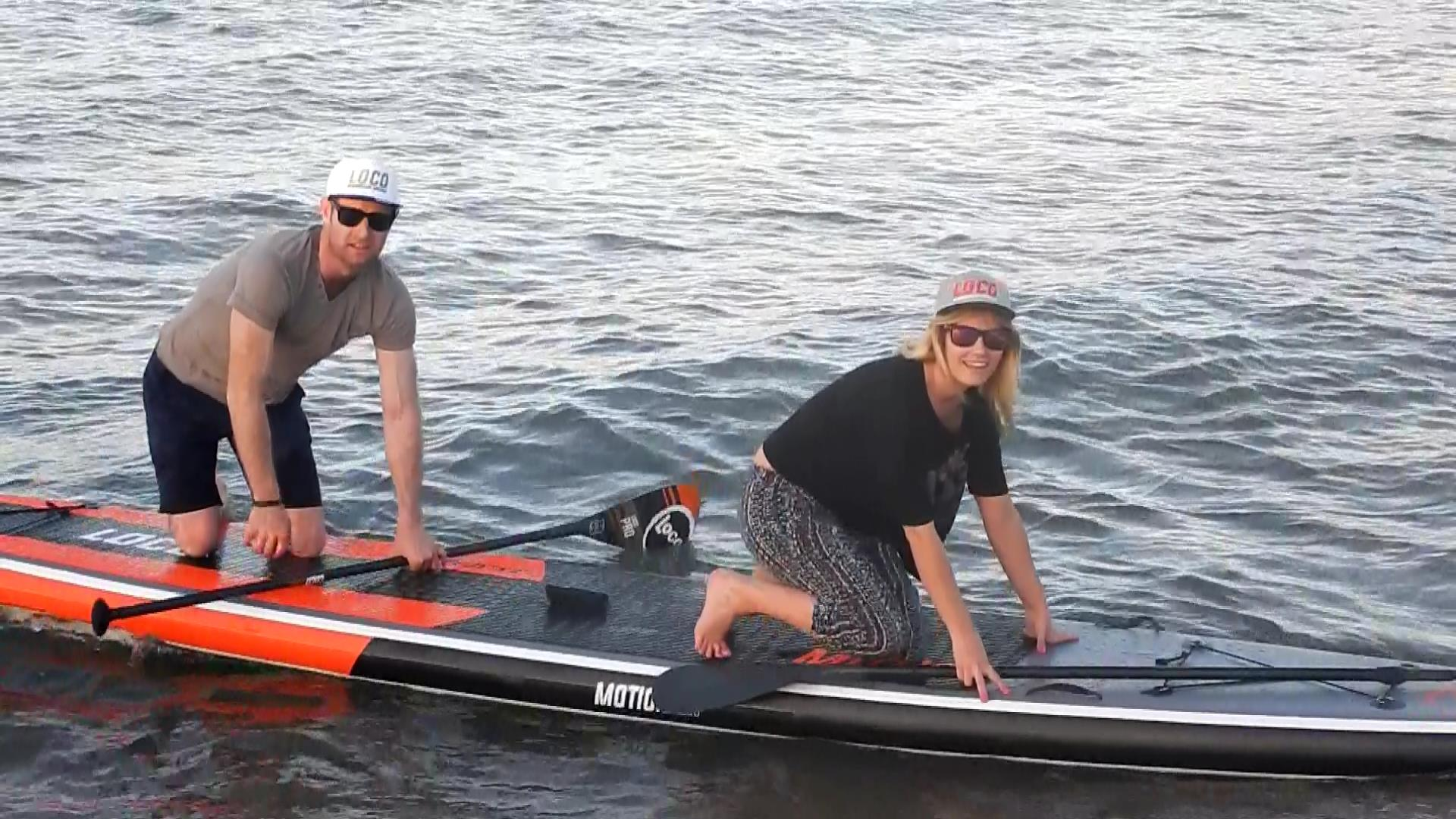 Couple exiting the water on the Loco Tandem Inflatable SUP
